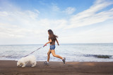 Young woman playing with her dog on the sea beach at sunny day
