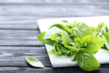 Green basil leafs with cutting board on black wooden table