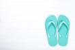 Pair of flip flops on white wooden background