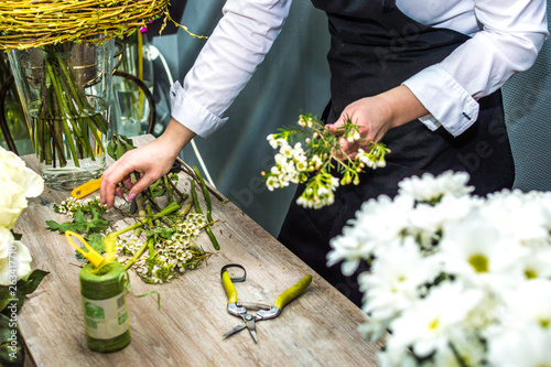 Process of creating a bouquet florist flower shop close-up. Woman hands and tool