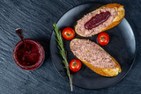 sandwich baguette with a paste on a black cement background with cowberry sauce, cherry tomatoes and rosemary