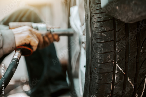 Close up of auto mechanic using tool to change tire while crouching at workshop. © dusanpetkovic1