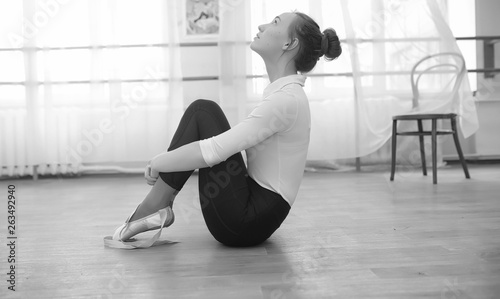 Young ballet dancer on a warm-up. The ballerina is preparing to perform in the studio. A girl in ballet clothes and shoes kneads by the handrails. © alexkich