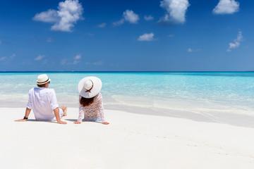 Verliebtes Paar sitzt am tropischen Strand mit türkisem Meer und genießt den Urlaub