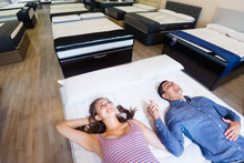 "Постер, картина, фотообои ""Family couple choosing mattress in furniture store"""