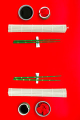 bamboo sticks, soy sauce, ginger for sushi and maki on red background top view © 9dreamstudio