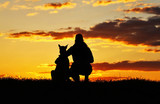 Silhouettes of girl and dog at sunset, breed Belgian shepherd Malinois, incredibly beautiful sunset, best friends together
