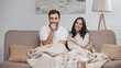 handsome sick man sitting on sofa with woman, coughing, taking glass of water and smiling while watching tv