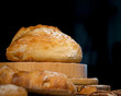 Fresh bread from rye and wheat flour on the table. Composition from a set of bread on a dark background. Bakery.