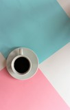 Cup of coffee on a pink and blue background. The view from the top.
