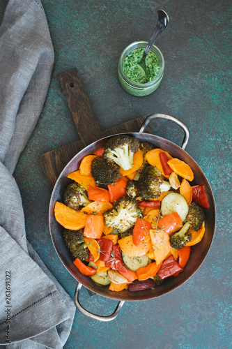 Pan of roasted different vegetables. Zucchini, sweet potatoes, carrots, broccoli, red bell vegetables. Dark green background, copy space - 263691322