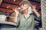 Nice stylish mature woman drinking delicious espresso