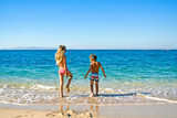 boy and girl on the beach go to the sea to swim on the shores of the Mediterranean Sea