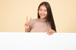 canvas print picture - Young Asian woman show victory sign with blank sign.
