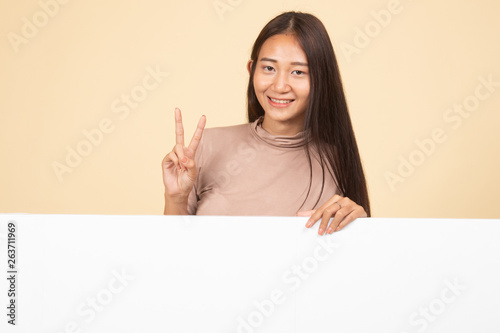 canvas print picture Young Asian woman show victory sign with blank sign.