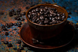 cup with coffee beans on dark table