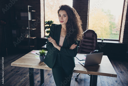 Leinwandbild Motiv Portrait positive cheerful satisfied entrepreneur content stand desk table computer laptop netbook leather armchair chair furniture dressed modern outfit long wavy curly hair hairstyle company loft