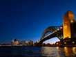 Harbour Bridge and Sydney city skyline at night against bright dark blue sky