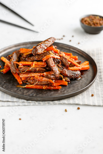 Chinese spicy Szechuan beef meal on a black plate with wooden sticks