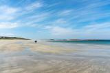 les silhouettes d'un couple qui marche seul sur une grande plage déserte de sable blanc
