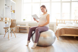 Full length portrait of pregnant woman sitting on fitness ball and using digital tablet during workout at home, copy space
