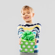 birthday, childhood and people concept - smiling little boy with gift box over grey background