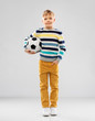 football, leisure and childhood concept - nice little boy in striped pullover with soccer ball over grey background