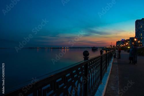 Spring night city Saratov quay under sunset. Street decorative lights and beautiful sky © welcomeinside
