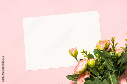Empty paper sheet and flowers on a purple background.