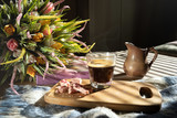 in bed, black coffee in a glass cup, a milk jug, crumbled pink chocolate on a blackboard and a bouquet of wildflowers, low light, horizontal frame