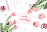 Mothers day message with cupcakes, tulips and gift on white background. Mothers day concept.