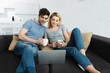 happy man holding cup and watching movie with attractive girl on laptop