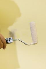 Hand applying paint on wall