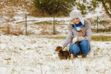 Woman playing with dogs during winter