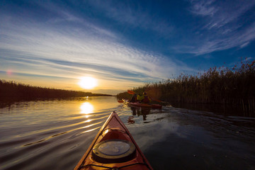 Bow of kayak and silhouettes of kayakers rowing on the lake at sunset