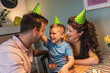 Happy family celebrating a birthday together at home.Young parents with son preparing birthday cap.