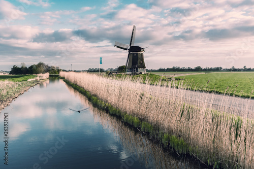 Windmill and Canal on Traditional Holland Landscape