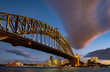 Illuminated Harbour Bridge at sunset with a dramatic cloud