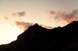The orange sun sets in the evening for the black silhouette of the mountain.
