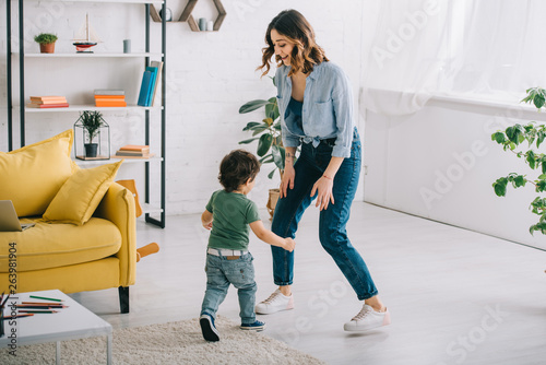 Full length view of smiling woman with son in living room © LIGHTFIELD STUDIOS