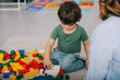 cropped view of mother and son playing with lego on carpet in living room