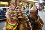 Street seller with asian conical wooden hats and baskets