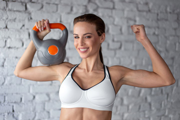 Young strong woman holding kettlebell on shoulder