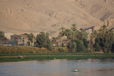Nile River, Egypt: Two men in a rowboat, farmers with their cattle, date palm trees, houses, and sand dunes along the west bank of the Nile River.