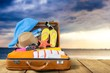 Retro suitcase with travel objects on wooden desk in beach background