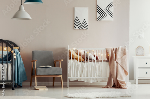 Fashionable retro armchair between two wooden cribs in cute twins nursery © Photographee.eu