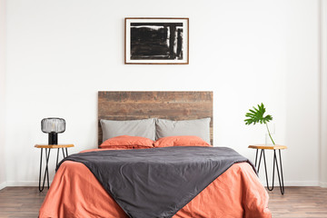 White minimal bedroom with wooden headboard and coral and grey bedsheets