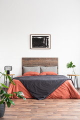 Minimal bedroom with wooden bed, plants and painting