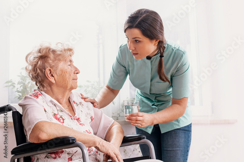 Senior grandmother on wheelchair, supporting nurse giving her glass of water © Photographee.eu