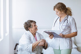 Young intern doctor with pad and stethoscope and elderly grandmother with cane